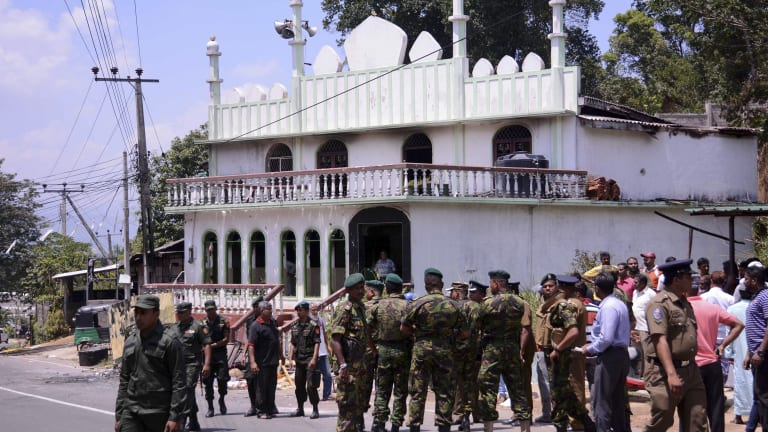 Security personnel stand near a vandalised Mosque in Digana, Sri Lanka after Buddhist mobs swept through the town burning at least 11 Muslim-owned shops and homes.