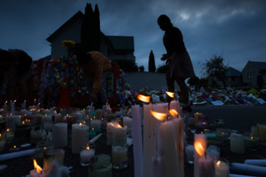 Candles are lit by school children  for the victims of Friday's attacks on Christchurch mosques.