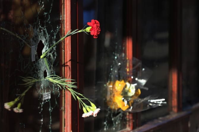 Flowers inside bullet holes in the window of Le Carillon restaurant, where the Paris terrorist attacks of November 2015 began to unfold.