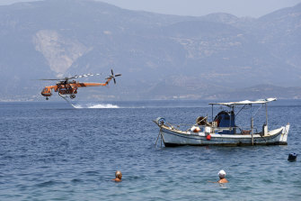 A helicopter fills up with water from the sea.