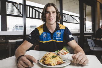 Canberra Demons player Alex Paech with his parma for a farmer at the Eastlakes club in Gungahlin.