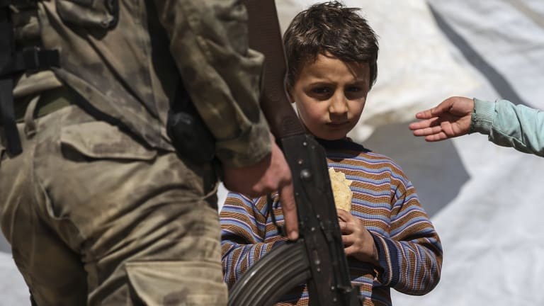 A Syrian child looks on as a Turkey-backed opposition fighter of the Free Syrian Army secures the streets of the north-western city of Azaz, Syria.