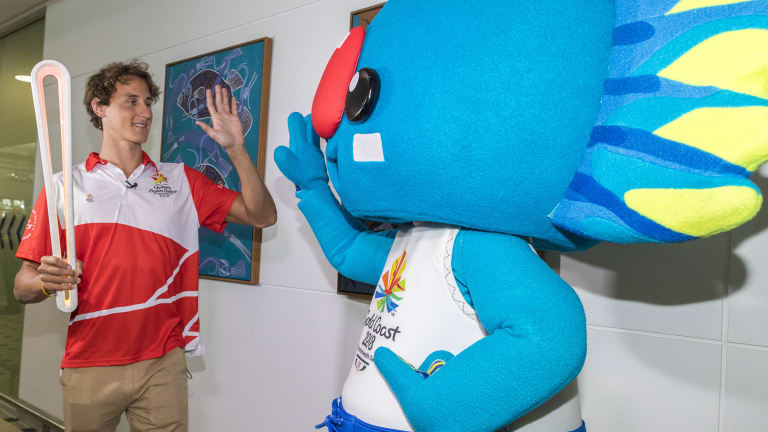 Cameron McEvoy arrives with the Queen's baton alongside Commonwealth Games mascot Borobi.