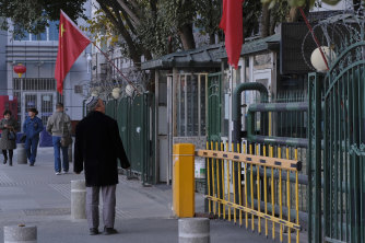 A man stares at a heavily fenced and gated mosque in the Xinjiang capital, Urumqi.