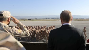 Russian President Vladimir Putin, right, watches the troops marching as he and Syrian President Bashar Assad visit the Hemeimeem air base in Syria in 2017.