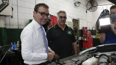 Liberal leader Steven Marshall speaks with Rocky Carbone, owner of an Ultra Tune car workshop on the eve of the South Australian election.