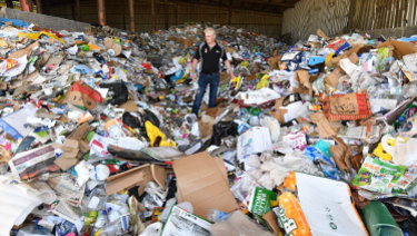 Wheelie Waste general manager Chris Philp among a day's worth of collected recycling from Kyneton.