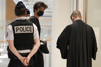 Juan Branco, a defence lawyer, centre in a black mask, arrives at the new court charged with trying cyber bulling cases.