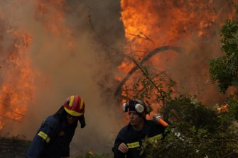 Firefighters battle blazes in Greece on Monday, during heatwaves exacerbated by extreme heat.