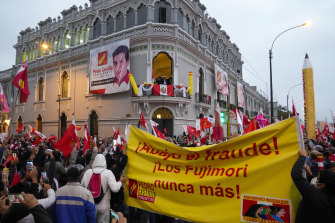 """Presidential candidate Pedro Castillo waves to supporters celebrating partial election results. The large banner reads """"the Fujimoris never again""""."""