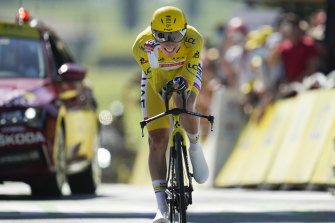 Slovenia's Tadej Pogacar, wearing the overall leader's yellow jersey, celebrates as he crosses the finish line of the twentieth stage of the Tour de France.