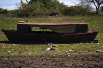 A bird walks past a boat sitting on the side of the almost dried up Payagua stream, a tributary of the Paraguay River.