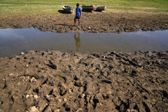 Cristopher Benegas, 12, fishes in what's left of the Payagua stream, a tributary of the Paraguay River, in Chaco I, Paraguay, on Friday.