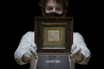 A Christie's staff member with Leonardo da Vinci's Head of a Bear.