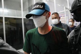 Thai police escort Thitisan Utthanaphon in Bangkok.