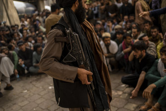 A Taliban fighter controls a crowd waiting to withdraw money from a bank.