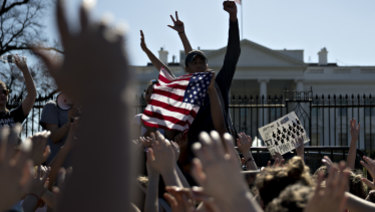 Students hold their hands up during a moment of silence during a protest against gun violence following the Florida massacre.