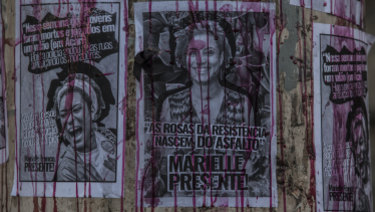 Posters depicting councillor MarielleFranco on a wall the day after she was murdered, in Rio.