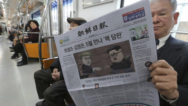 A passenger reads a newspaper with headline of a planned summit meeting between North Korean leader Kim Jong Un and U.S. President Donald Trump on a  subway train in Seoul, South Korea.