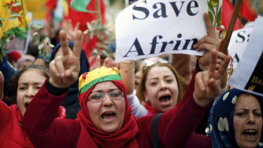 Kurdish demonstrators chant slogans as they flash victory signs during a protest against the operation by the Turkish army aimed at ousting the US-backed Kurdish militia from the area in Afrin, Syria.