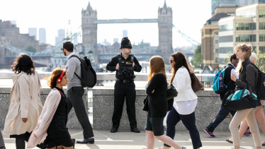 Commuters walk past a City of London Police officer after a terrorist attack last year.