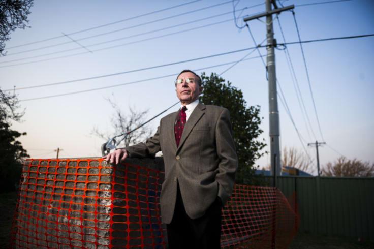 Leo Dobes of the Griffith Narrabundah Community Council with the concrete pillar.