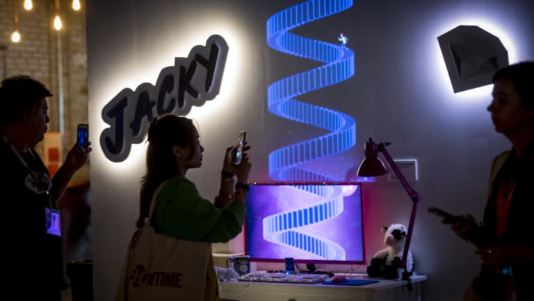 Attendees use smartphones to take photographs while viewing the YouTube story exhibit during the South By Southwest (SXSW) conference in Austin, Texas,  on Saturday.