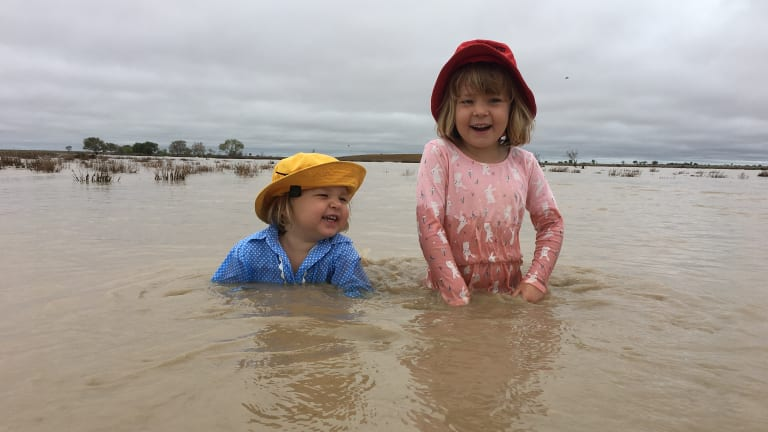 Two-year-old April Batt and her four-year-old sister Daisy Batt were nearly as happy as their parents when the creeks started to run muddy water at Hillview, Muttaburra after 50mm of rain on Saturday night.