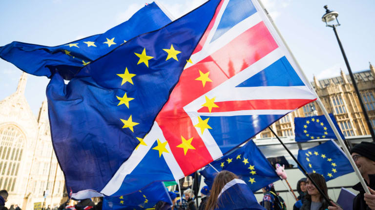 Brexit protesters wave flags made up of a European Union flags and British Union flags, otherwise known as a Union Jack, outside the Houses of Parliament in London.