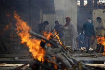 Multiple funeral pyres of COVID-19 victims burn as relatives perform last rites at a crematorium in Delhi, India.