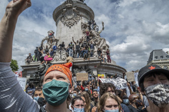Anti-racism protesters stand on the monument in Place de la Republique in Paris on June 13.