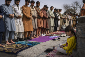 An Afghan girl working as a shoe cleaner sits in the street while men pray during Friday prayers in Kabul, Afghanistan, last week.