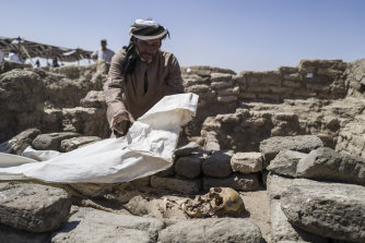 A worker covers skeletal remains found at the site of a 3000-year-old lost city in Luxor, Egypt.