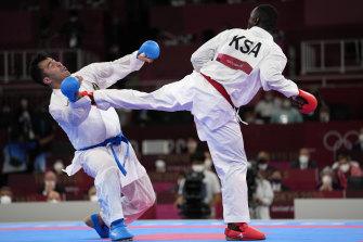 Sajad Ganjzadeh of Iran, left, is injured while competing against Tareg Hamedi of Saudi Arabia in their men's kumite +75kg gold medal bout.