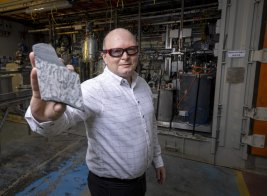 Jared Osborne, general manager of Rio Tinto's laboratory in Melbourne that worked out how to process Jaradite, holds a lump of the rare mineral.