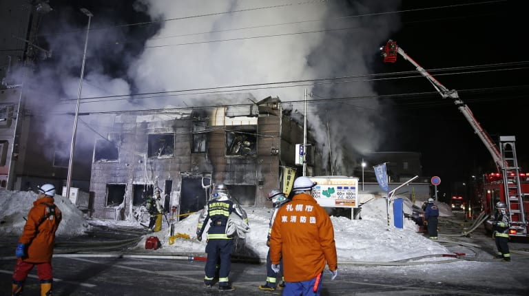 Firefighters work at the scene of the fire in Sapporo, northern Japan.