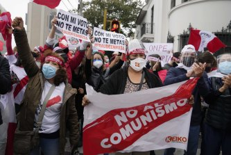 """Supporters of presidential candidate Keiko Fujimori hold a banner reading """"No to communism"""" and """"fraud"""", outside the official vote council office, in Lima."""