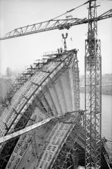 The highest segment on the roof of the Sydney Opera House is moved into position in 1967.