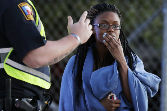 An employee wrapped in a blanket talks to a police officer after she was evacuated from the FedEx distribution centre.