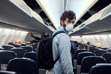 Shot of a young man wearing a mask and boarding an plane