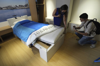 Journalists look at cardboard beds at the athletes village of the Tokyo Olympics and Paralympics prior to the start of the Games.