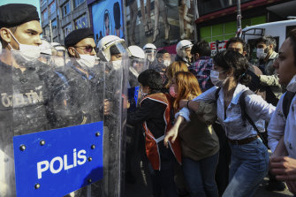 Turkish police officers in riot gear hold back protesters in Istanbul on Tuesday.