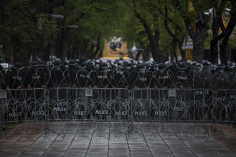 Police form a line behind razor wire in Bangkok.