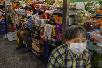 Fruit vendors wear protective masks as they wait for customers at a local market in Beijing.