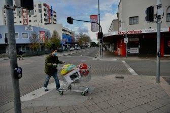 A shopper wheels a trolley through quiet Fairfield streets.