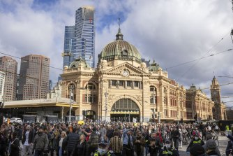 Anti-lockdown and anti-vaccine protesters out the front of Flinders Street Station on Saturday.