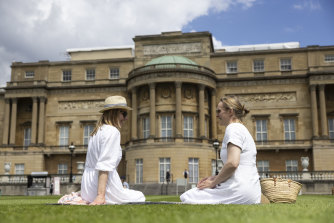 Visitors picnic on the lawn in the newly-opened gardens at Buckingham Palace this week.