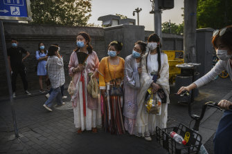 Chinese women wear traditional clothing and protective masks as they wait to cross a road in a tourist area during the May holiday in Beijing.