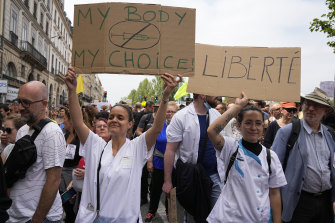 Nurses hold placards as they march during an anti-vaccine protest in Paris on the weekend.