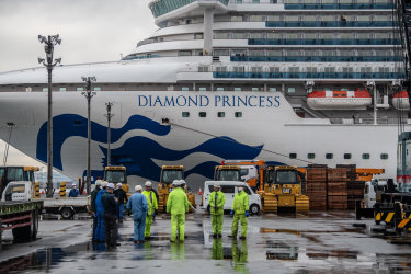 YOKOHAMA, JAPAN - FEBRUARY 13: Workers gather before removing machinery stored on the dock next to the Diamond Princess cruise ship at Daikoku Pier where it is being resupplied and newly diagnosed COVID-19 cases taken for treatment as it remains in quarantine after a number of the 3,700 people on board were diagnosed with coronavirus, on February 13, 2020 in Yokohama, Japan. At least 219 passengers and crew onboard the Diamond Princess cruise ship have tested positive for COVID-19 making it the biggest centre of the virus outside China. Japan has also so far diagnosed 28 other people with the illness, some of whom are evacuees from Wuhan, and has announced measures to ban entry to foreign travelers from Zhejiang alongside an existing ban on non-Japanese nationals coming from Hubei. (Photo by Carl Court/Getty Images)